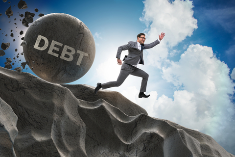 Man chased by large ball of debt.